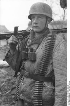German paratrooper near Monte Cassino, Italy, Jan 1943, carrying a machine gun and ammo belts and wearing light winter tunic usually issued to mountain troops.