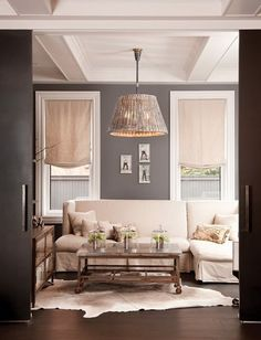 i like the burlap looking drapes with the gray walls and dark hardwood floor, with plenty of white accents and shiny hanging lamp. Not into the rug.