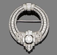 An Art Deco diamond brooch, ca 1930.  The openwork circlet pierced & set with three tapered rows of single-cut diamonds, to a central cartouche set with similarly & baguette-cut diamonds collet-set at the centre with a larger old brilliant-cut diamond, diamonds approx 2.85ct total, length 4.4cm.
