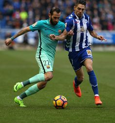 Barcelona's defender Aleix Vidal (L) vies with Deportivo Alaves  forward Ruben Sobrino during the Spanish league football match Deportivo Alaves vs FC Barcelona at the Mendizorroza stadium in Vitoria on Feburary 11, 2017. / AFP / CESAR MANSO