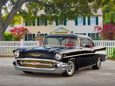 1957 Chevrolet Bel Air Black 3/4 Front View On Pavement By White Fence And House