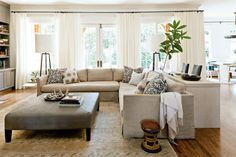 Lindsey simplified the seating with a few large yet sleek pieces. A collection of patterned pillows maximizes visual interest. She strategically framed the view by hanging draperies over the walls instead of the windows.