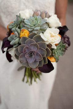 Succulents Bride bouquet mixed in with orange ranunculus and cream roses. The mix of succulents and flowers softens the bouquet.