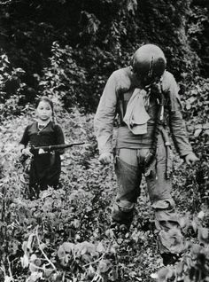 A US Air Force Lieutenant is held captive by a young North Vietnamese girl soldier, 1967.