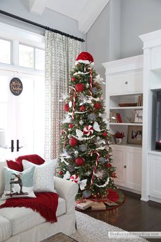 candy-cane-christmas-tree ~ love the oversized ornaments & candy canes on a tall tree