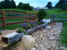 Pretty entry to a long country driveway with repurposed old tree trunk as a raised flower bed.