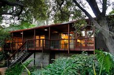 The Norton House, designed 1954 by famed architects Buff & Hensman. Mid-century modern with walls of glass, use of wood with cork flooring. Dramatic arroyo setting with stream, bridge and mature landscaping. Pasadena.