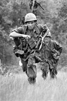 Two infantrymen sprint across the clearing in War Zone D where a U.S. battalion is trapped under automatic weapons fire from surrounding Viet Cong troops, 50 miles northeast of Saigon, Vietnam.