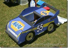 Cardboard race car for NASCAR-themed birthday party via Urban Hoot. Tires are made from small black paper plates and CDs that are attached with velcro.