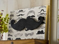 Want a completely unique and unusual piece of wall art? This DIY mustache canvas is definitely an original - made with Mod Podge and glitter paint!