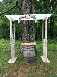Antique white door arbor with flowers on top and whiskey barrel with unity sitting on top