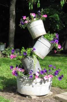 Stack a tipsy bucket tower as a garden focal point.