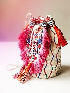 Tiadoro Bucket Bag   Tribal-inspired bucket style bag featuring colorful bead and fringe accents. Leather trim with tassels, this bucket bag has a drawstring closure and braided leather straps. Inside has zip and slip pockets.