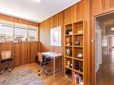 Built in cuboards under window, hidden by panelling with display shelf on top.