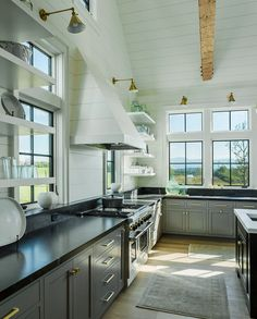 Two-toned kitchen with grey lower cabinets and white shiplap hood and white open shelves. Roundtree Construction