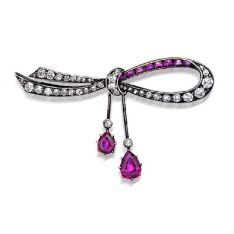 Ruby and diamond brooch, early twentieth century, designed as a tied ribbon claw set with graduating old cut diamonds and channel set rubies, suspending two knife edge bars with pear shaped ruby and diamond terminals, mounted in silver and gold.