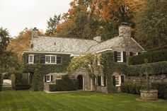 Stone, slate roof, white windows, black shutters, meticulously maintained landscaping - via For the Home / Rodney Smith's studio, photo Adam Golfer for The Wall Street Journal