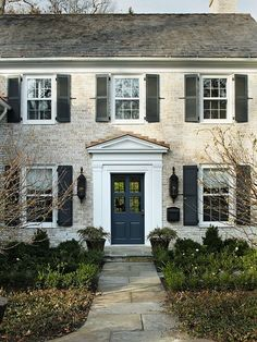 Love the white wash brick, gray shutters and dark blue door