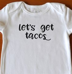Lets Get Tacos Bodysuit . This short sleeved white bodysuit has a choice of size and text color. Its very soft and perfect for babies! *Three nickel-free snaps on reinforced panels *Expandable shoulders *100% cotton rib *Machine washable Size Length Weight 0-3M 21.5-24 9-12.5 lb 3-6M
