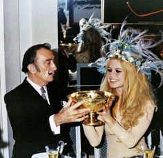 Salvador Dali + Brigitte Bardot drinking champagne out of a golden chalice.