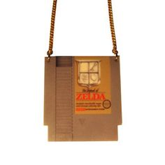 Iconic and brilliant The Legend of Zeldaoriginal NES Nintendo games console cartridge design retro pendant, fashioned from printed 3mm acrylic, on 41cm split gold plated curb chain. Measures approximately 50mm x 45mm. Nickel and lead free.