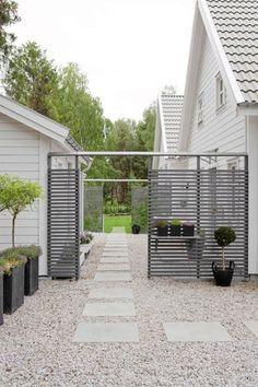 porte de jardin en lattes de bois grisâtre et une allée en dalles