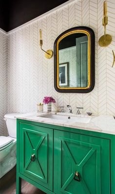 Charming contemporary powder room stands out with an emerald green washstand fitted with a cream marble countertop fitted with a sink and polished nickel faucet fixed beneath a gold and black vanity mirror mounted to a wall clad in Serena Bathroom Interior, Home Interior, Interior Design, Interior Decorating, Eclectic Bathroom, Decorating Ideas, Bathroom Furniture, Bad Inspiration, Bathroom Inspiration