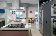 """Para a criação do amplo living, foram demolidas as paredes entre sala de estar, sala de jantar, hall, copa e cozinha. """"Fizemos a cozinha grande, com ilha central, que pode ser isolada por painéis de vidro leitoso"""", diz o arquiteto André Becker."""