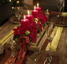 Poinsecje są idealne do stworzenia dekoracji stołu i wykreowania szczególnej atmosfery. Tę prostokątną aranżację na drewnianej tacy tworzą czerwone mini poinsecje, gałązki ostrokrzewu, małe jabłuszka oraz wstążki przysłaniające gąbkę florystyczną. Ustawione w rzędzie cztery świece oświetlają świątecznie nakryty stół.
