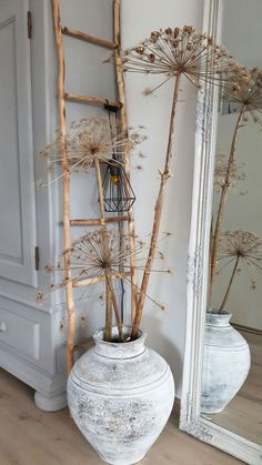 De grandes fleurs séchées agrémentent un pot ancien