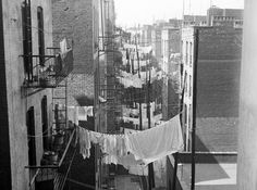 A view down an alley, as rows and rows of laundry hang from tenements ca. 1935-1941. Seen looking west from 70 Columbus Avenue or Amsterdam Avenue at 63nd Street.