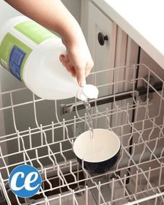 How To Clean Your Dishwasher In 3 Quick And Easy Steps Comment Nettoyer Votre Lave-Vaisselle En 3 tapes Rapides Et Faciles A hand pouring white vinegar into the dishwasher