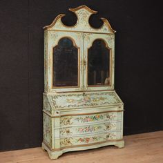 """Price: 4300€ Venetian bureau from the early 20th century. Furniture in carved, lacquered and painted wood with floral decorations. Venetian bureau built in two bodies. Lower half with three drawers, inside with two drawers, one door and a central """"secret"""" compartment. Upper half with two doors and recessed mirrors, with two drawers, one door and ten openings. It presents several falls of lacquering and some shortcomings. #antiques #antiquariato Visit our website www.parino.it"""