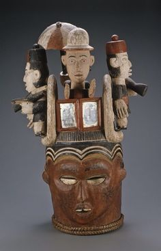 Africa | Janus-faced helmet mask with four superstructure figures. Ejagham people. ca. 1930-70. | Wood, skin pigment, iron, fiber, mirrors.