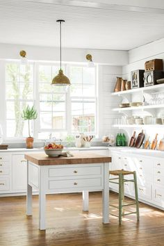 The Kitchen - Charming Tennessee Mountain Cottage - Southernliving. The all-white, open kitchen is outfitted with limestone countertops, brass fittings, and antique radios that belonged to the homeowners' grandmothers.