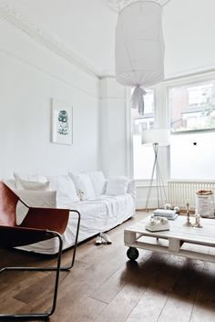 All-white living room with fabric pendant light, wooden pallet coffee table, and leather sling chair.