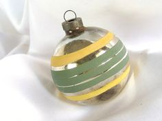 The large, yellow and green striped silver Christmas ornament has an unusual shade of soft olive green. It complements the soft yellow stripes.