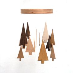 Wooden tree mobile. Trees are handcrafted from birch plywood and are stained assorted shades. Approximately 15 trees on mobile in various