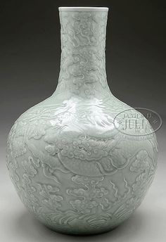 """Ching dynasty, 19th century, China. Finely carved with a dragon, pearls, and clouds. Sea green celadon glaze. Ch'ien Lung mark on the base. SIZE: 22-1/2"""" h x 13"""" dia."""