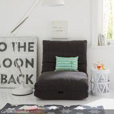 Ein Schlafsessel oder eine Klappmatratze ist in erster Linie ein praktisches Möbelstück. In einem weißen Raum mit moderner Deko und dekoriert mit bunten Dekokissen…