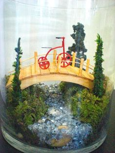 Tricycle left on the bridge of a beautiful Japanese garden. This is a great and unique gift for a garden or plant lover and a wonderful way to bring outdoors in whether at home or in the office. This garden contains live moss.