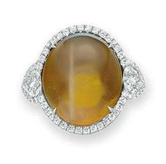 A CAT'S EYE CHRYSOBERYL AND DIAMOND RING   Set with an oval cabochon cat's eye chrysoberyl, weighing approximately 33.55 carats, flanked on either side by a heart-shaped diamond, all within a circular-cut diamond surround, mounted in platinum