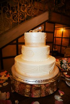 Elegant three tier ivory wedding cake with glass slipper cake topper // Limelight Photography