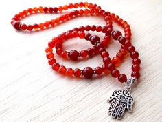 Carnelian Necklace, 108 Mala Beads, Buddhist Prayer Beads, Yoga Om Necklace, Red Hamsa Necklace, Energy Necklace - Motivation, Protection ♥ All the XtraClaire´s creations are made with high quality gemstones in order to you can enjoy to the maximum their properties.This necklace measures 35 cm/ 14 inch from top to bottom and includes TierraCast metal components, high detailed and pewter free. ♥ Add me to your favorite shop to stay updated on all the new products that I post.♥ ♥ More C...