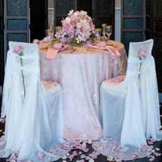 Sweetheart Table featuring Pink Lamour Linen/Napkins, Ivory Chiffon Chair Covers/Ties, and Silver Calista Overlay #wedding