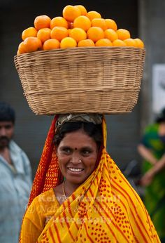 Indian woman carrying a basket of oranges on her head to the market