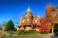 Ornate red brick Victorian mansion on corner lot in Arkansas