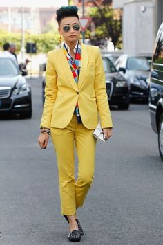 Esther Quek. bright orange suit with bold patterned shirt, black flats.