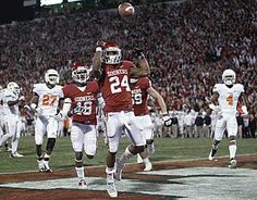 Oklahoma running back Brennan Clay tosses the football after scoring the game-winning touchdown in overtime during the Bedlam matchup against Oklahoma State.  Sooners win 51-48
