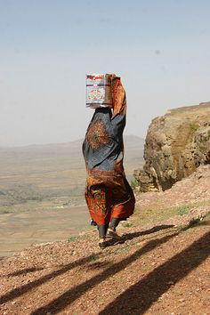 Veiled woman carrying a box on her head - Yemen by Eric Lafforgue, via Flickr